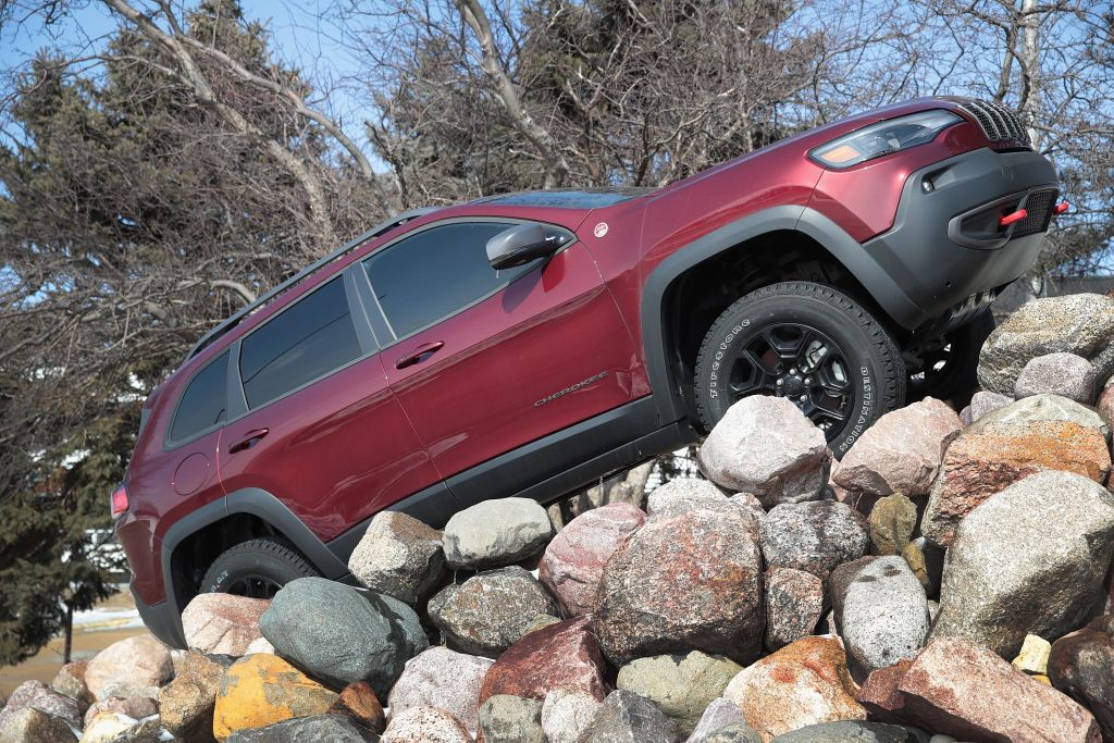A red Jeep Cherokee driving up a pile of rocks