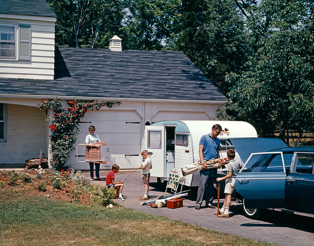 A 1960s family packing their vehicle and camper for a road trip