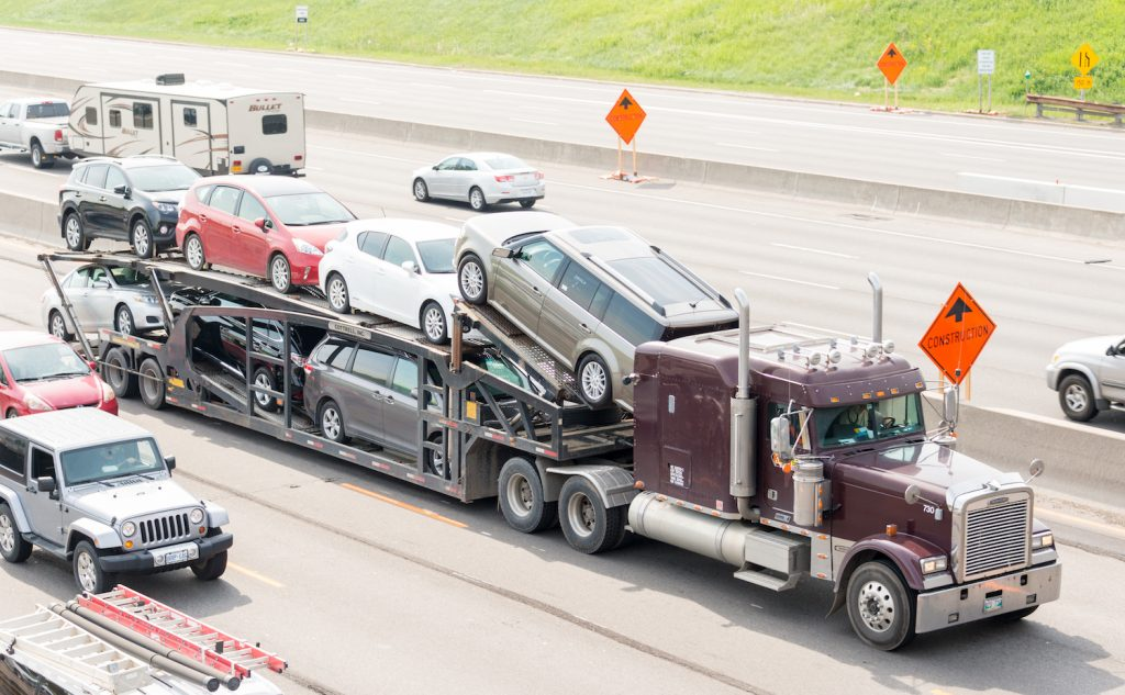 A trailer truck transporting cars being shipped.