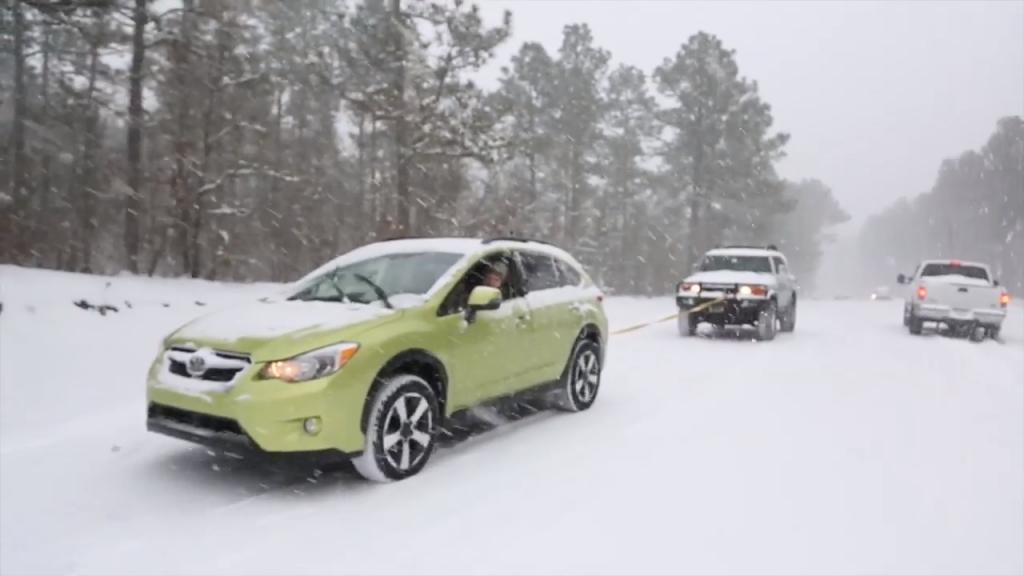 A still photo of the Subaru Crosstrek towing an FJ Cruiser in the snow