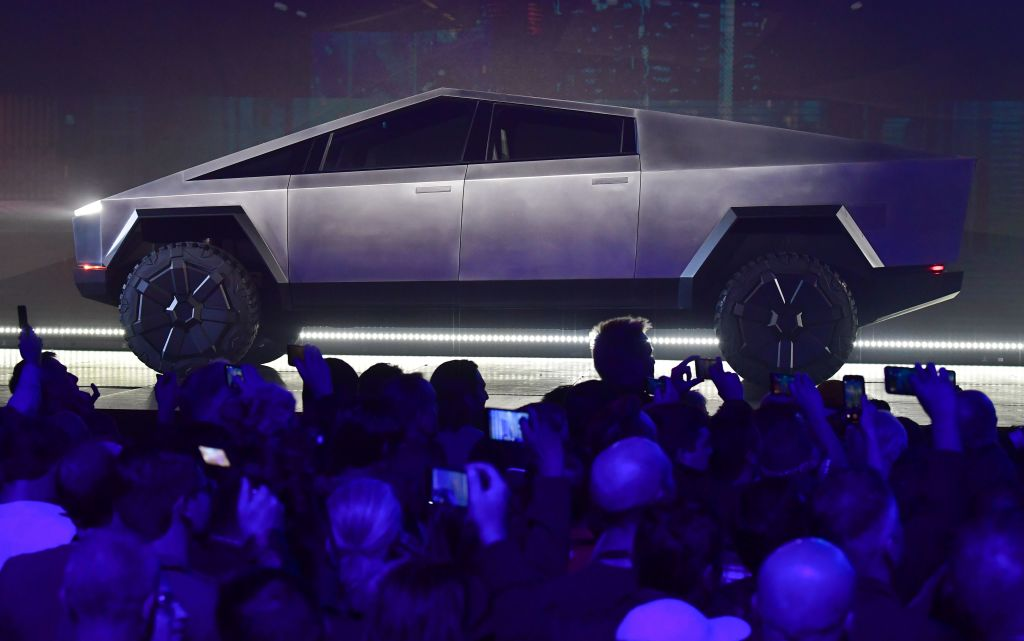 Tesla's stainless steel, angular Cybertruck displayed on a stage with a live audience.