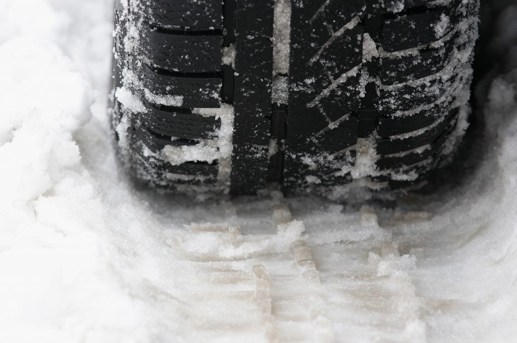 A car tire in the snow. |