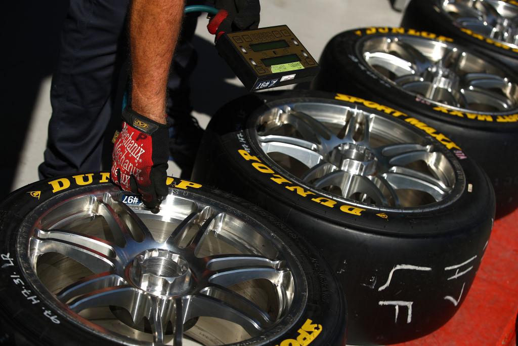 A crew member of the Red Bull Ampol Holden Commodore ZB checks tire pressure