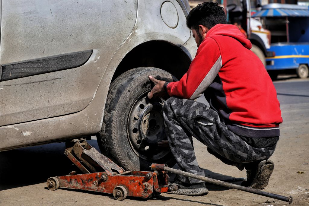 A man changes a dirty tire on the side of the road
