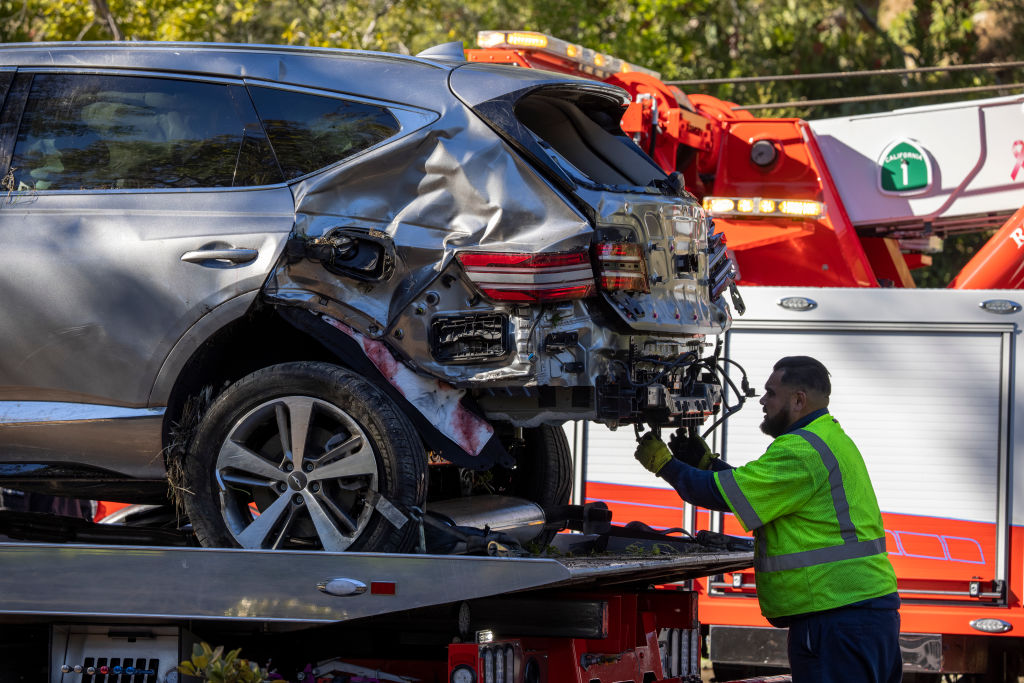 A tow truck operator secures the car that golf legend Tiger Woods was driving when seriously injured in a rollover accident