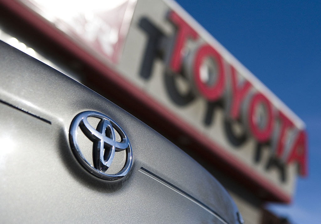 Close up of a Toyota logo on the bumper of a grey vehicle. Out of focus, in the background, is a Toyota dealership sign