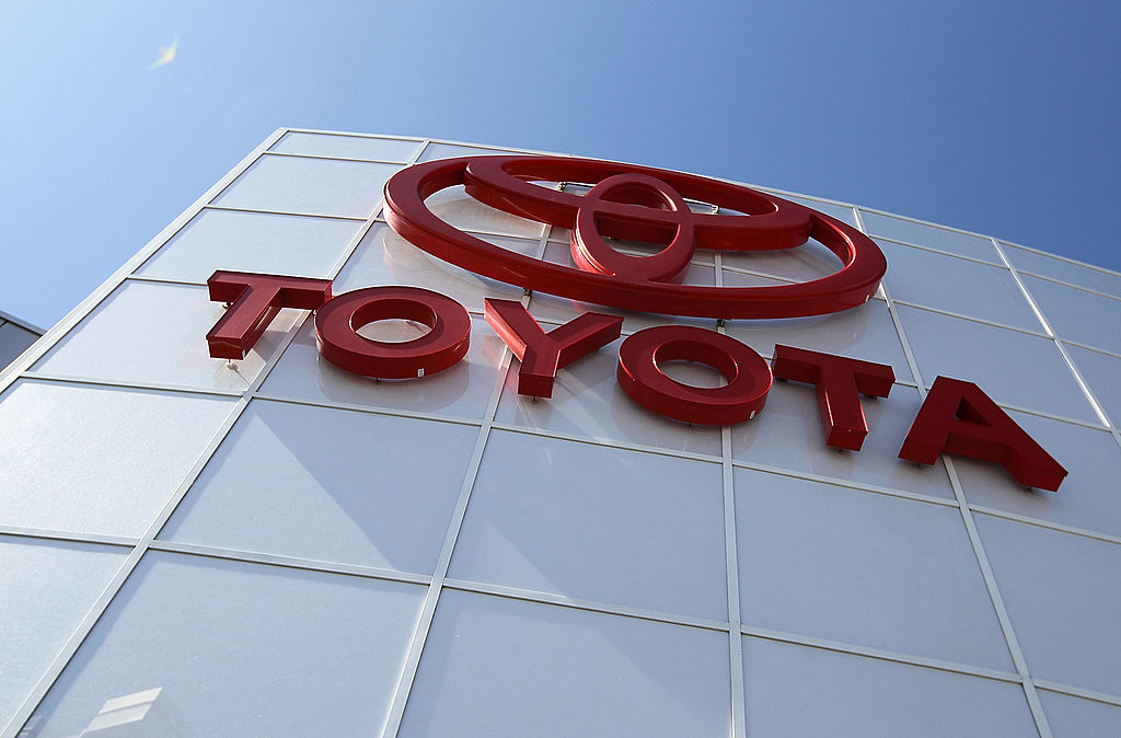 A red logo of the Lexus parent brand, Toyota, on the side of a white building