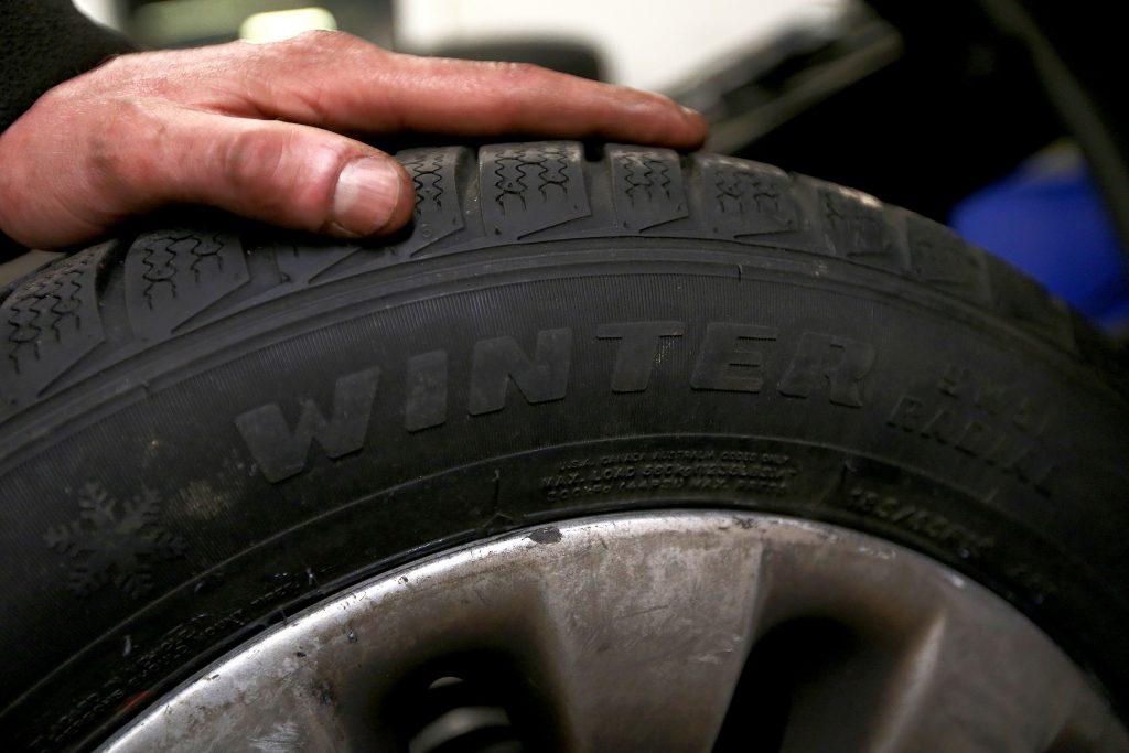 A car mechanic holds a winter tire at a garage.