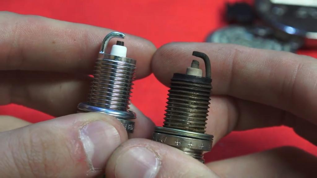 A good spark plug next to a worn spark plug
