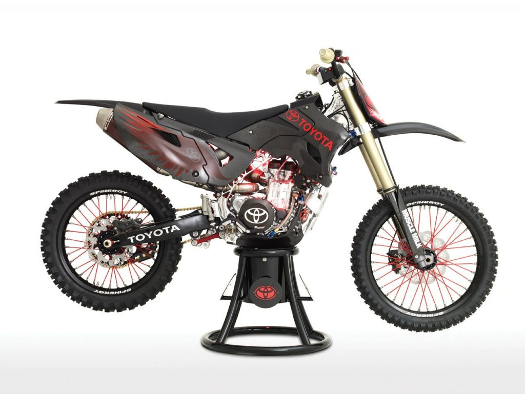 Toyota JGRMX motorcycle concept on a stand against a white back drop