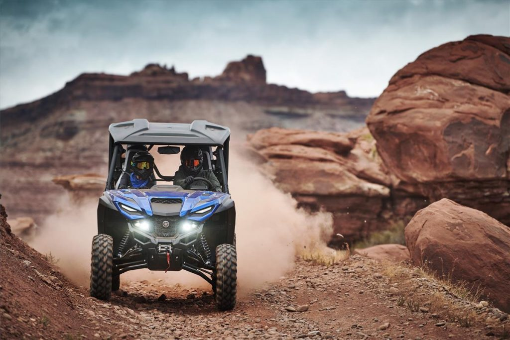 a Yamaha wolverine side-by-side UTV in the desert navigating red and rocky terrain