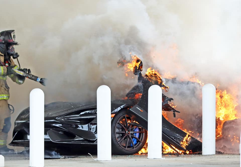 An image of a McLaren 765 LT on fire at a gas station.