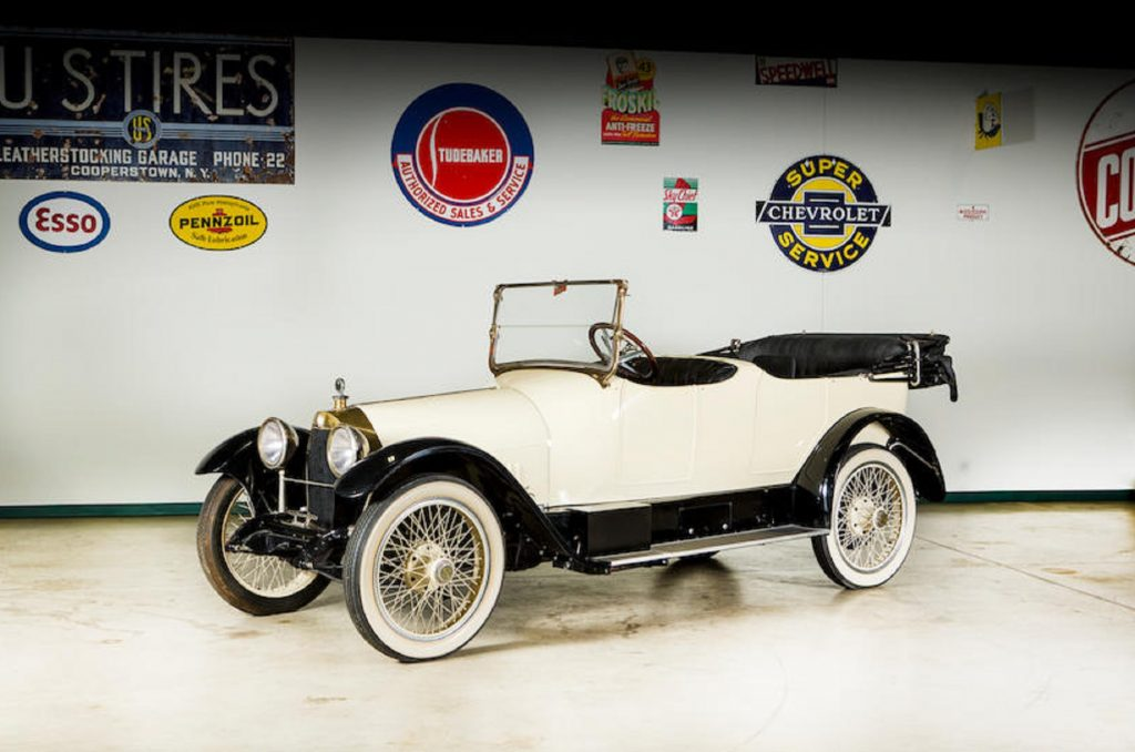 A white 1916 Owen Magnetic Tourer in a garage with various car logos