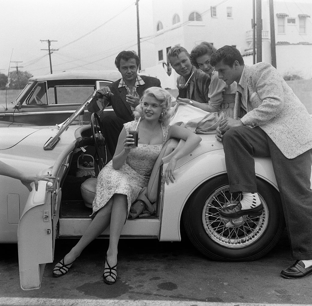 Jayne Mansfield in her Jaguar surrounded by friends