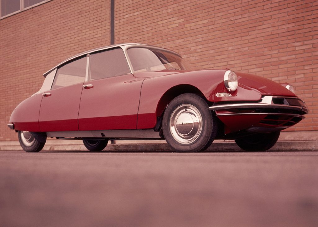 A red 1960 Citroen DS 19 by a brick building