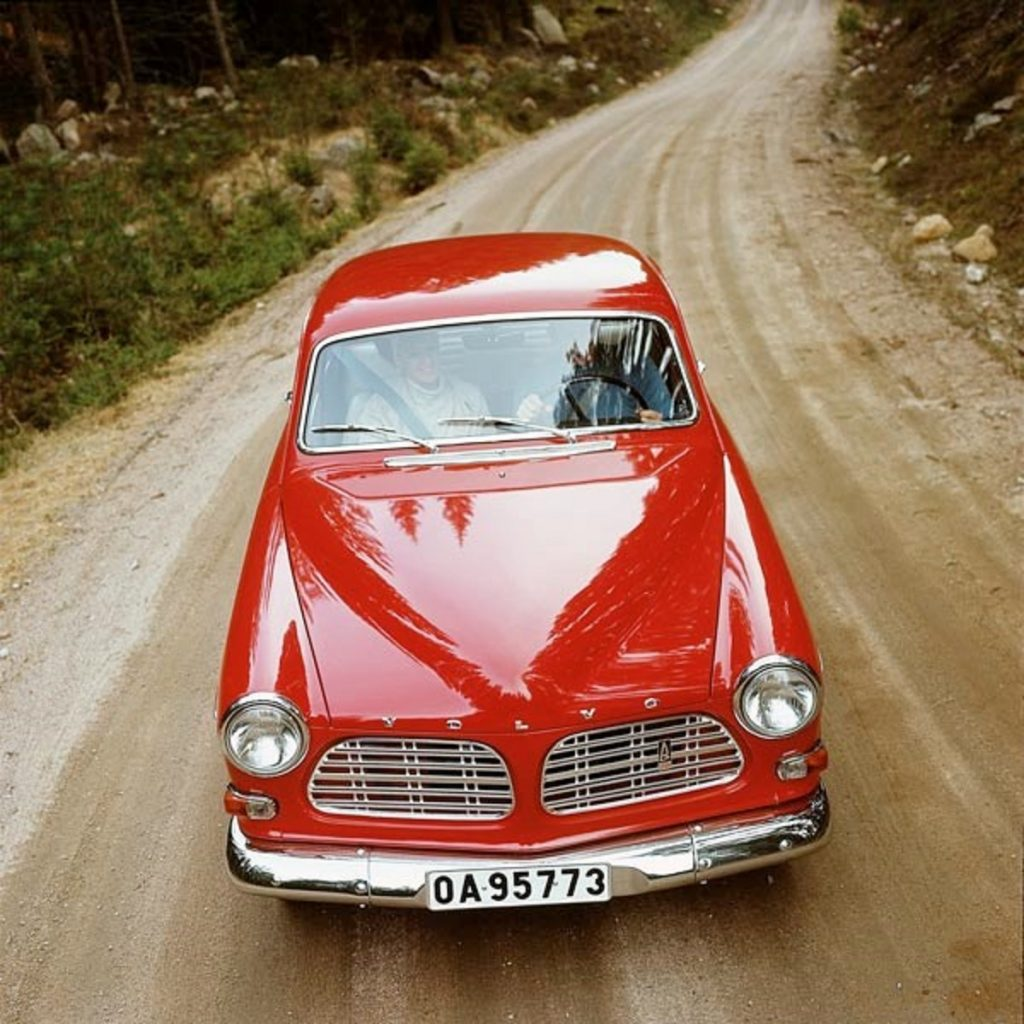 A red 1961 Volvo Amazon drives down a dirt road