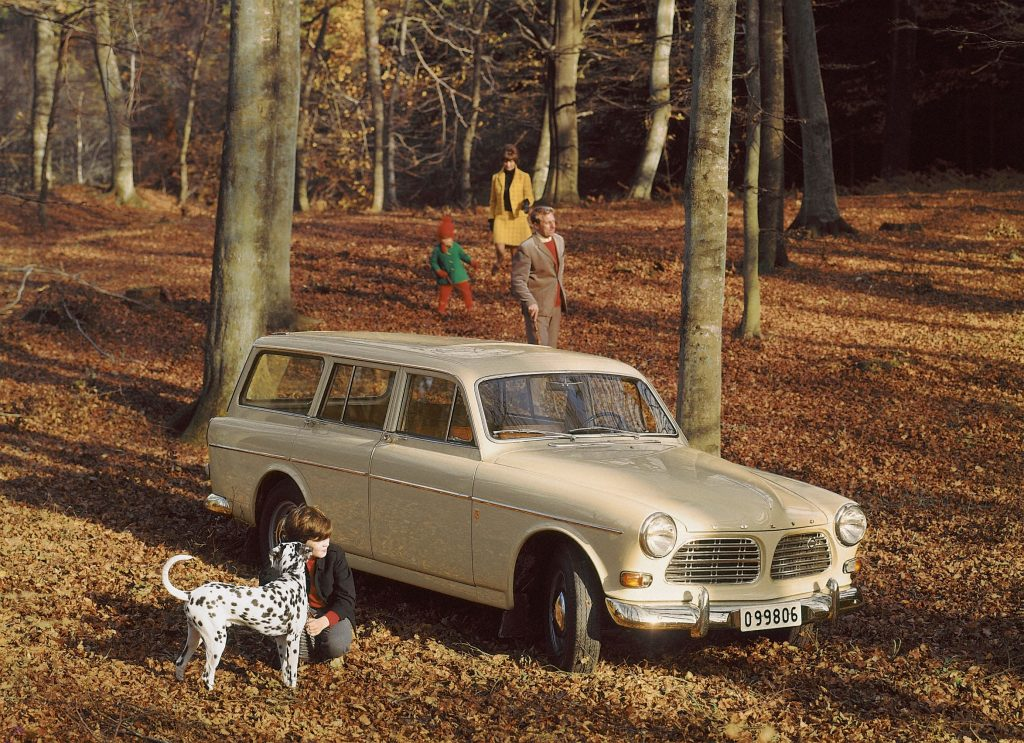 A family in a fall forest with a white 1962 Volvo 'P220' Amazon wagon