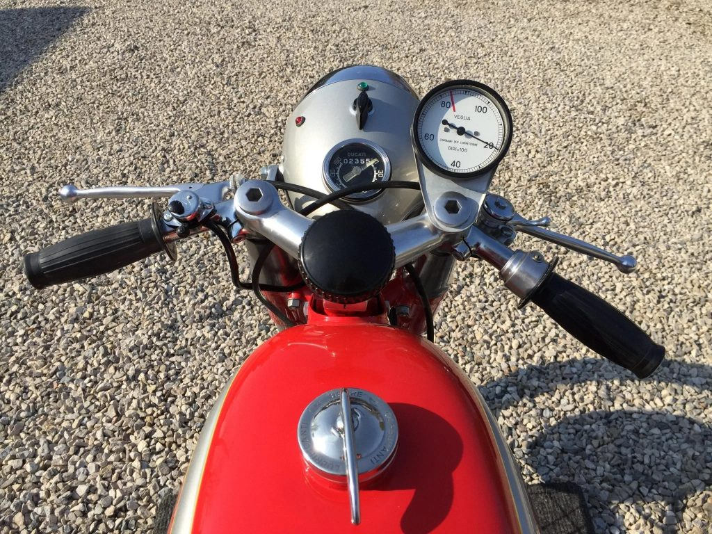 The handlebars, fuel tank, and dials of a red 1965 Ducati Mach 1 on a gravel driveway