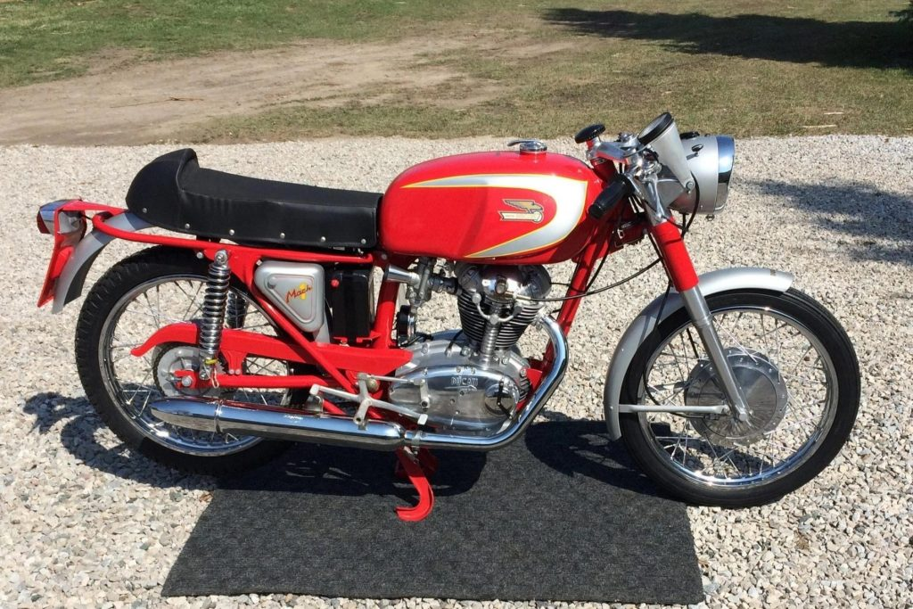 The side view of a red-and-silver 1965 Ducati Mach 1 on a gravel driveway