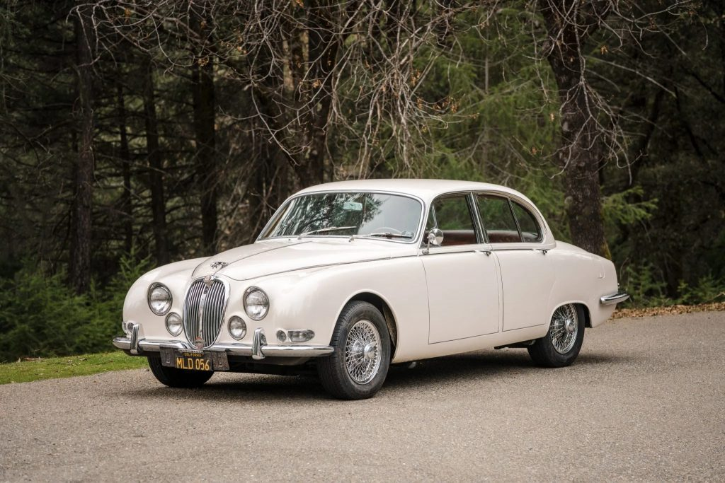 A white 1965 Jaguar S-Type 3.8 parked next to a forest