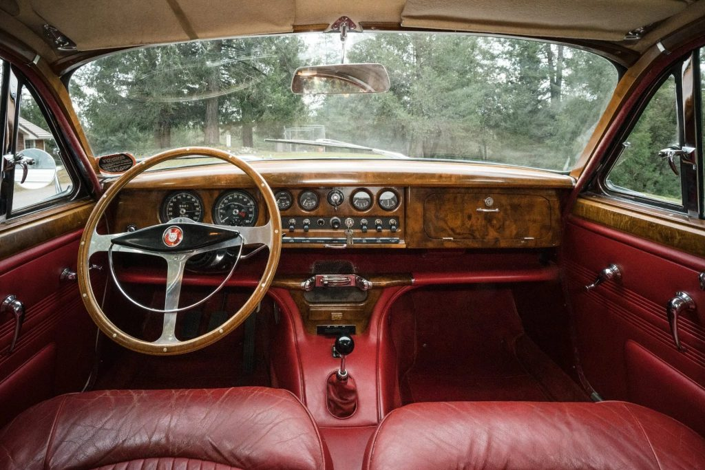 The red-leather-upholstered and wood-trimmed interior of a 1965 Jaguar S-Type 3.8