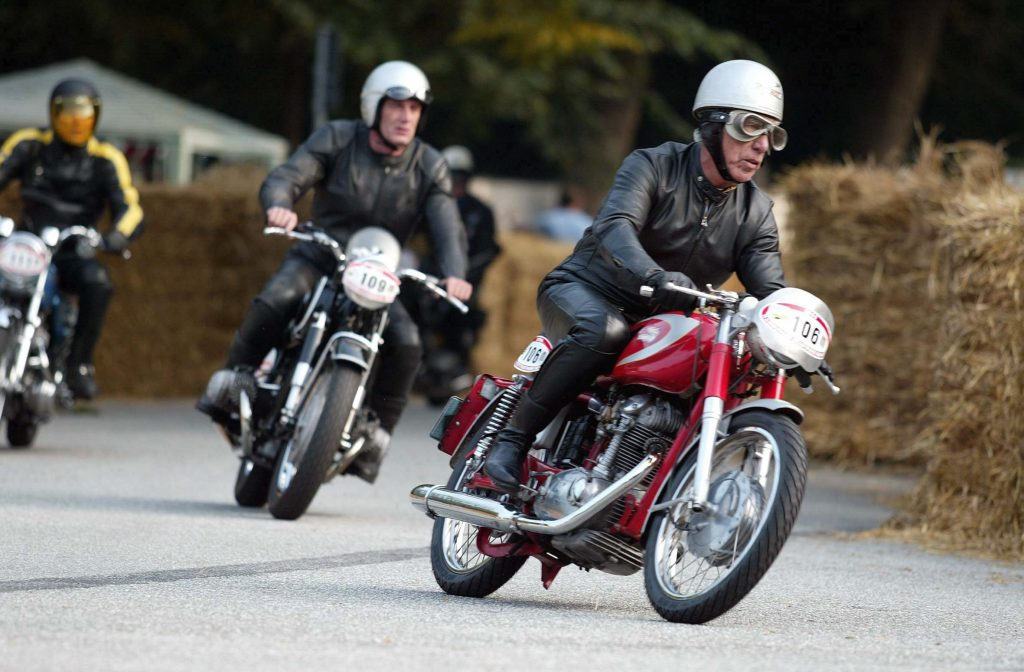 A black-clad rider on a red-and-silver 1967 Ducati Mach 1 leads 1966 BMW R50 and 1969 Norton Commando at a 2004 Hamburg, Germany race
