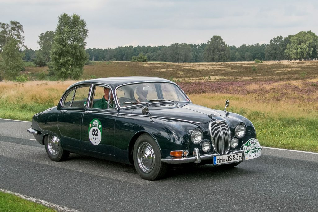 A dark-green 1968 Jaguar S-Type driving in a German road rally