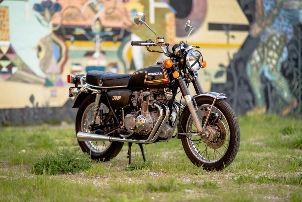 A black-and-gold 1973 Honda CB350F with an X-taped headlight in a yard next to a graffitied wall