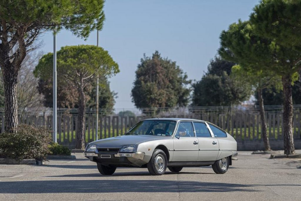 A silver 1975 Citroen CX 2000 parked on a tree-lined driveway