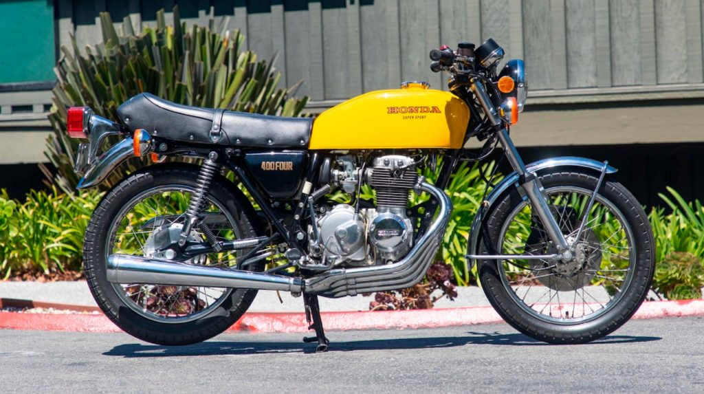 The side view of a yellow 1976 Honda CB400F Super Sport in a parking lot