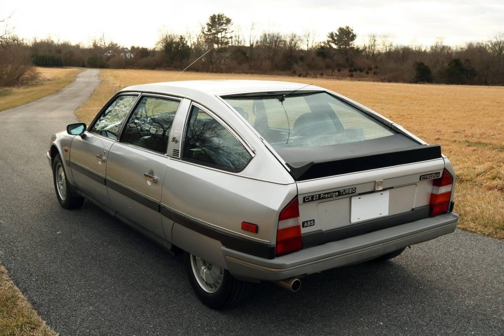 The rear 3/4 view of a silver 1986 Citroen CX 25 Prestige Turbo on a winding road