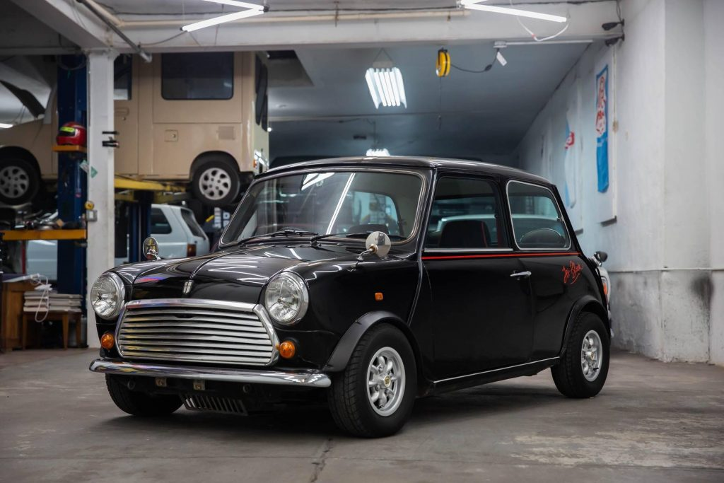 A black 1988 Rover Mini Jet Black Edition in a car workshop garage