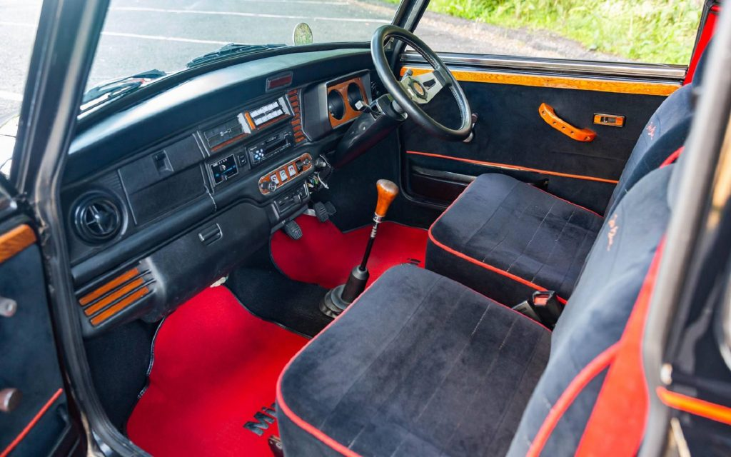 The red-and-black-velour-upholstered front seats and wood trim in a 1988 Rover Mini Jet Black Edition