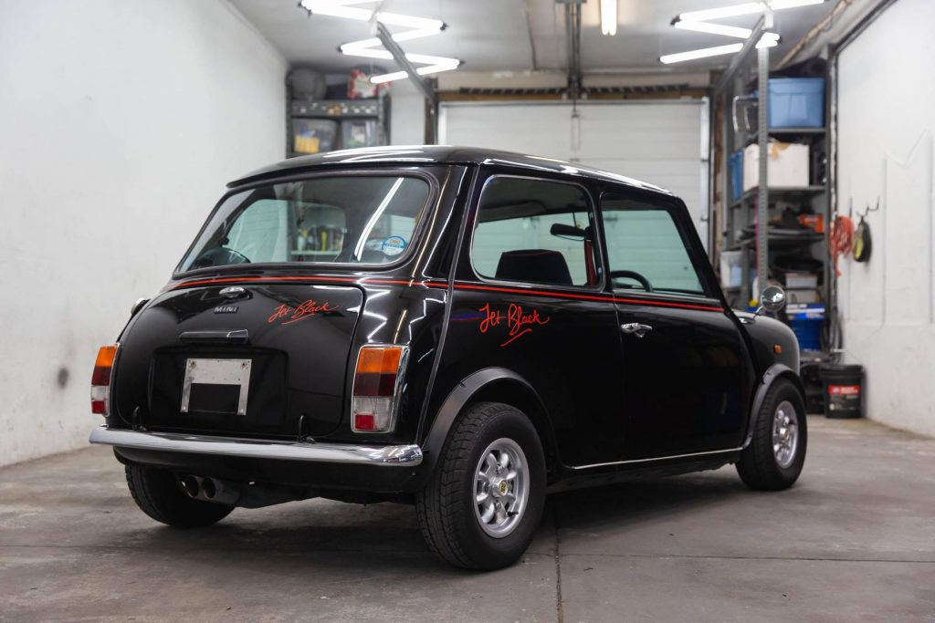 The rear 3/4 view of a black 1988 Rover Mini Jet Black Edition in a car workshop garage