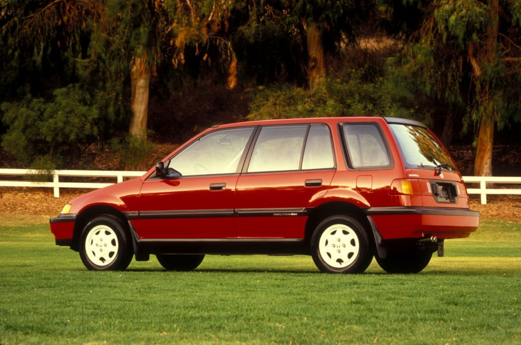 The side 3/4 view of a red 1989 Honda Civic 4WD Wagon in a grassy field