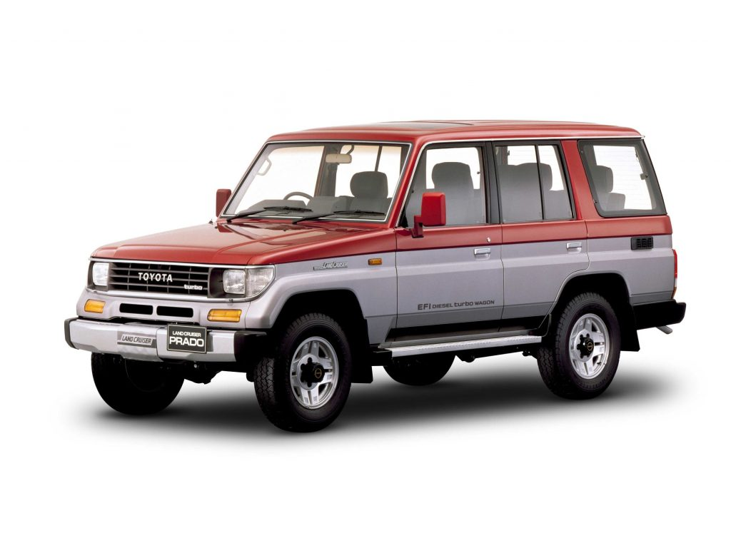 A red-and-gray 1990 Toyota Land Cruiser Prado
