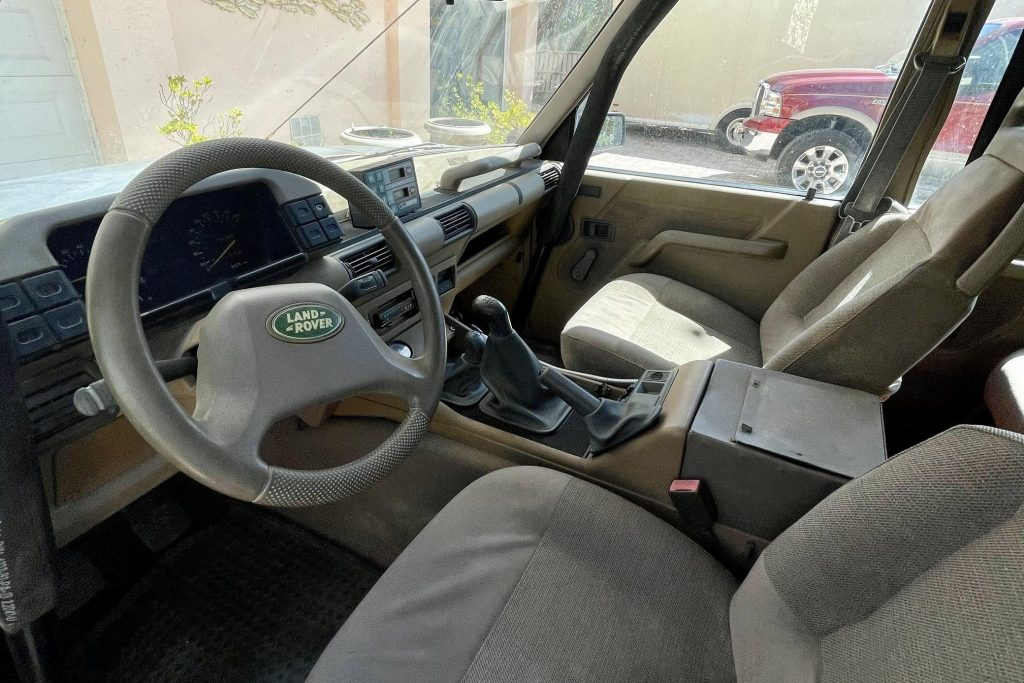 The tan-cloth front seats, tan dashboard, and front roll cage of a 1992 Land Rover Discovery Camel Trophy
