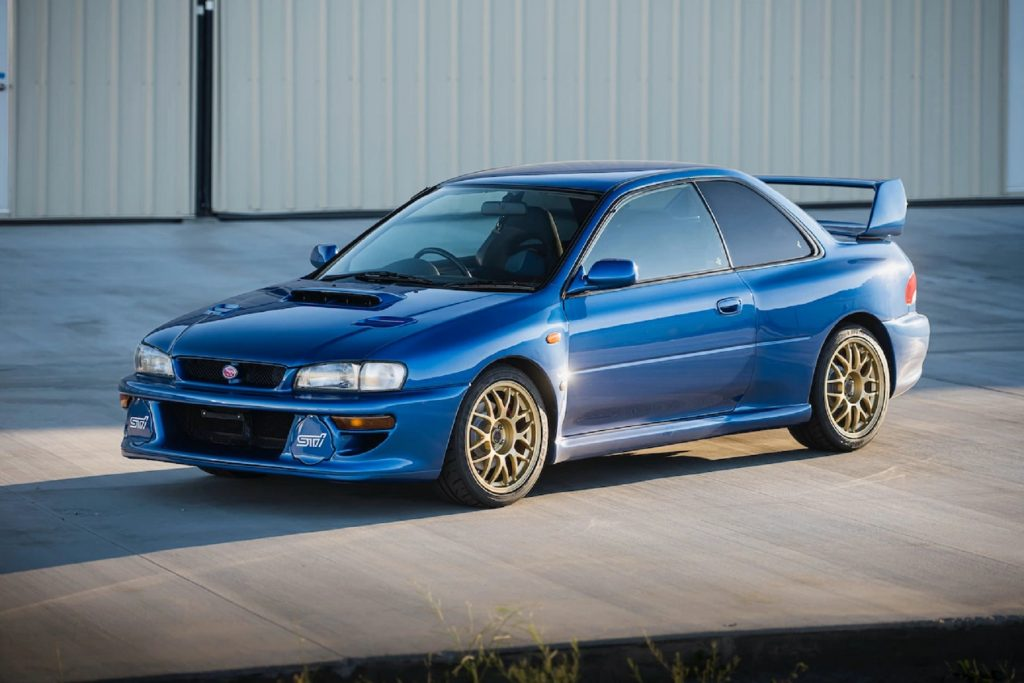 A blue 1998 Subaru Impreza 22B STi parked by a warehouse