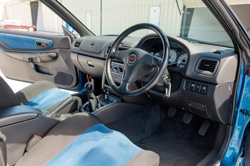 The blue-and-black Recaro front seats and dashboard of a 1998 Subaru Impreza 22B STi