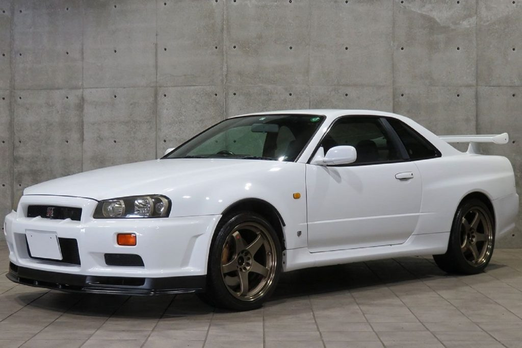 A white 1999 R34 Nissan Skyline GT-R by a gray stone wall