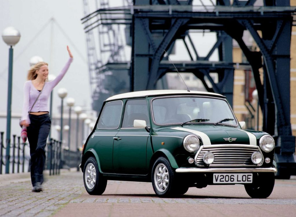 A woman walks next to a green-with-white-stripes 2000 Rover Mini Cooper by a European bridge