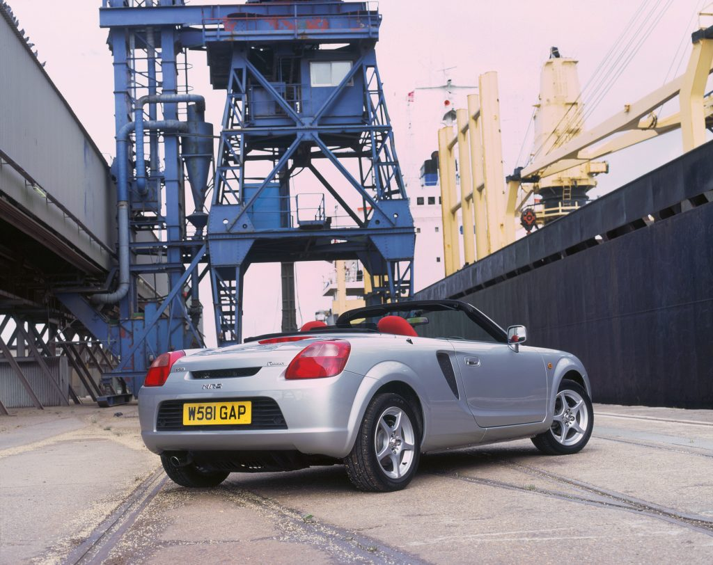 A silver 2000 Toyota MR2 Roadster convertible parked in a shipping yard