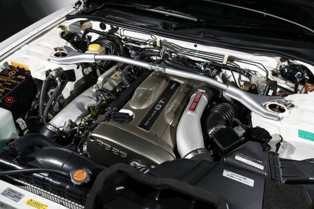 The engine bay of a white 2002 R34 Nissan Skyline GT-R V-Spec II Nur showing the gold engine cover