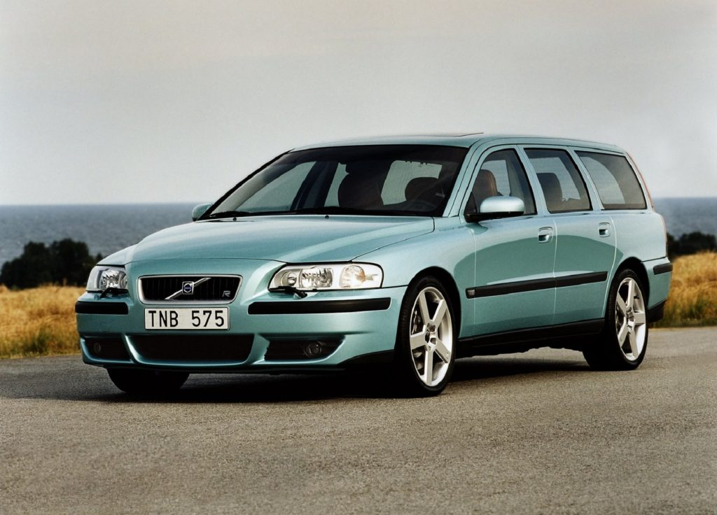 A teal 2003 Volvo V70R on a road by a body of water