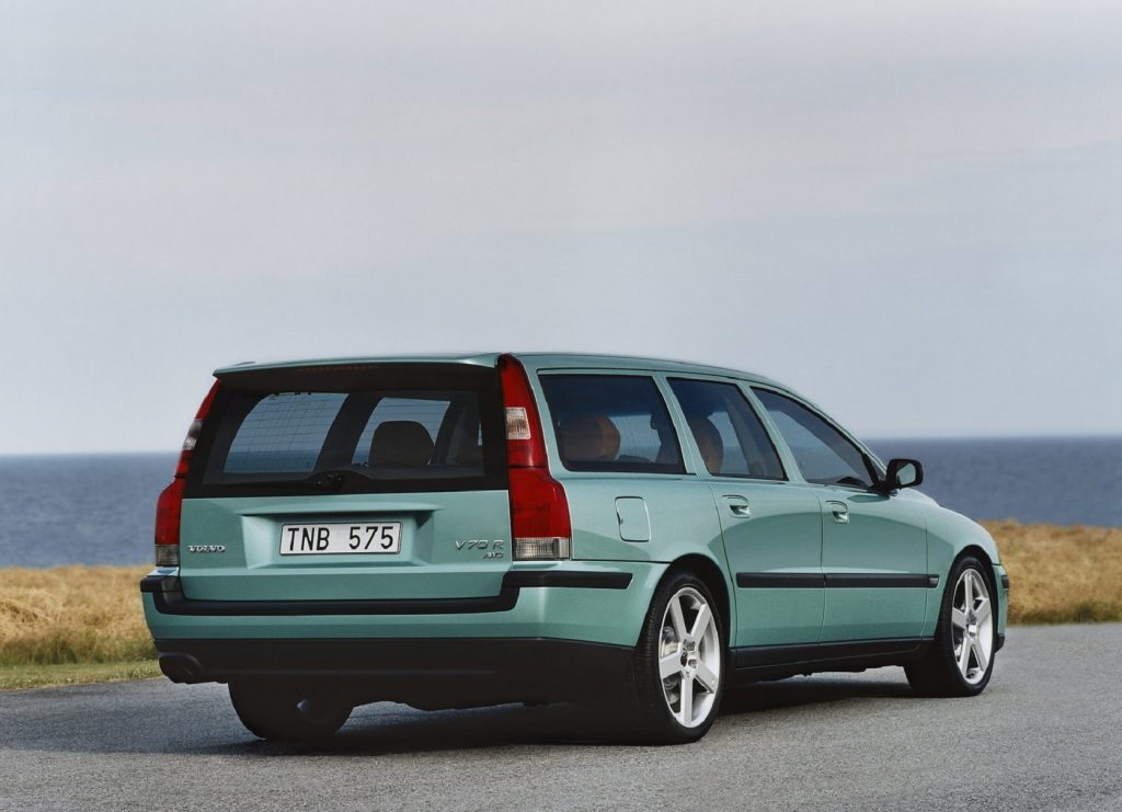 The rear 3/4 view of a teal 2003 Volvo V70R parked by a body of water