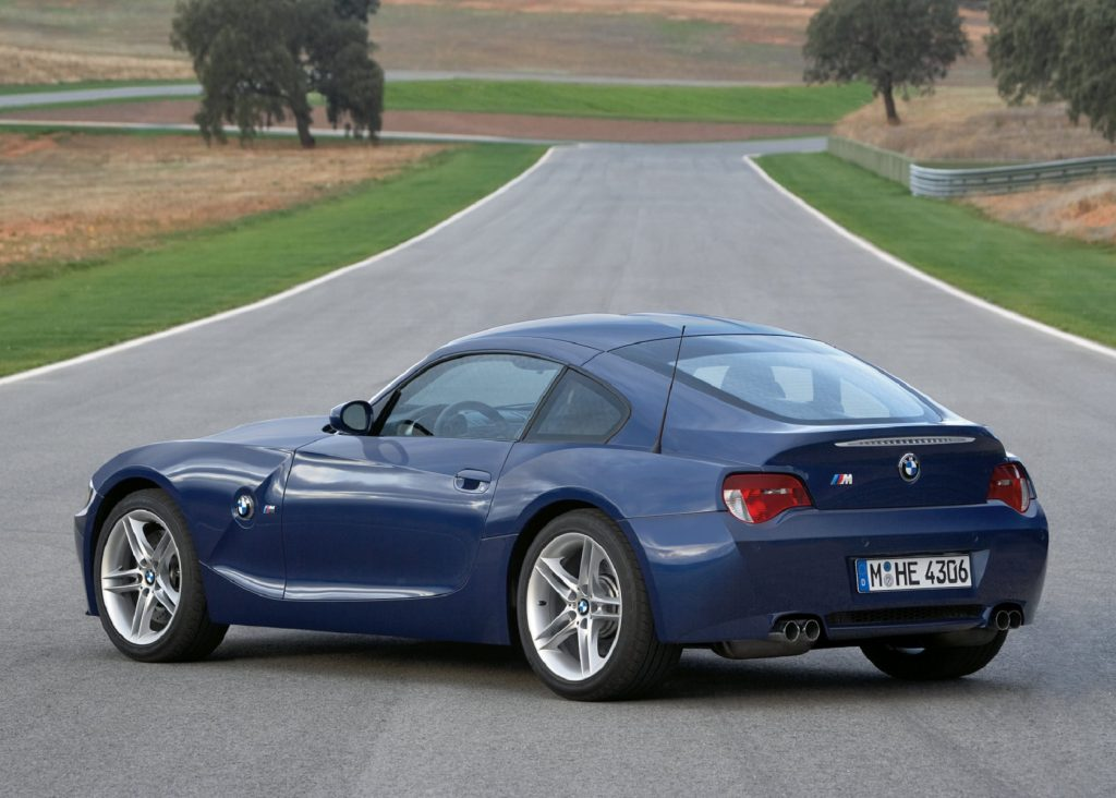 The rear 3/4 view of a blue 2006 BMW Z4 M Coupe on a racetrack