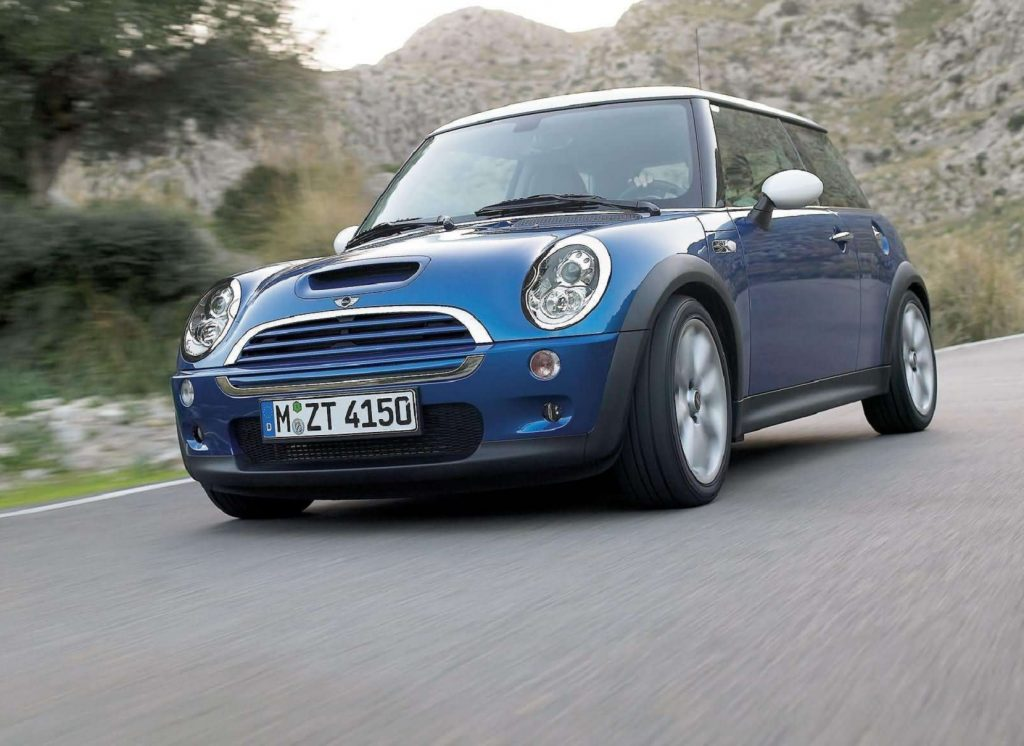 A blue 2006 'R53' Mini Cooper S drives down a valley road
