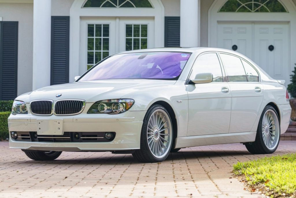 A white 2007 BMW Alpina B7 parked in the driveway of a white house