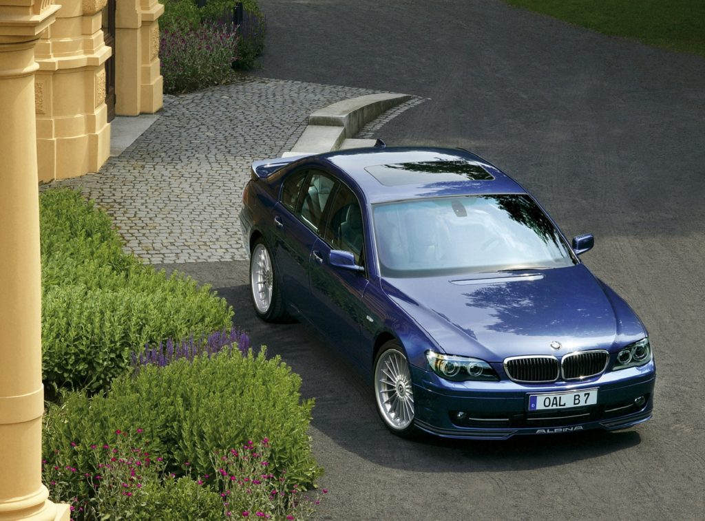 An overhead front 3/4 view of a blue 2007 BMW Alpina B7 in front of a yellow villa