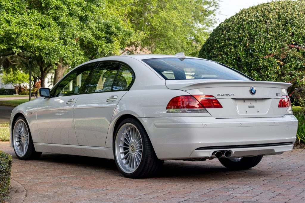 The rear 3/4 view of a white 2007 BMW Alpina B7 parked on a bush-lined driveway